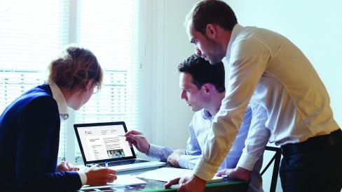 Trije sodelavci gledajo v zaslon računalnika.